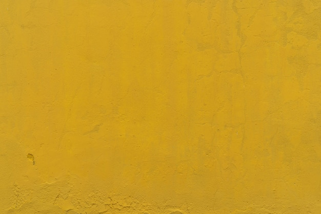 De gele ruwe concrete achtergrond van de muurtextuur. gele cement uitstekende abstracte achtergrond. lege muurruimte voor tekst.