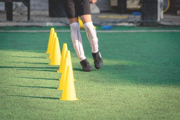 De gele sport teller van opleidingskegels op hoogte van het voetbal de groene gras voor de opleidingssessie van de kinderenvoetbal