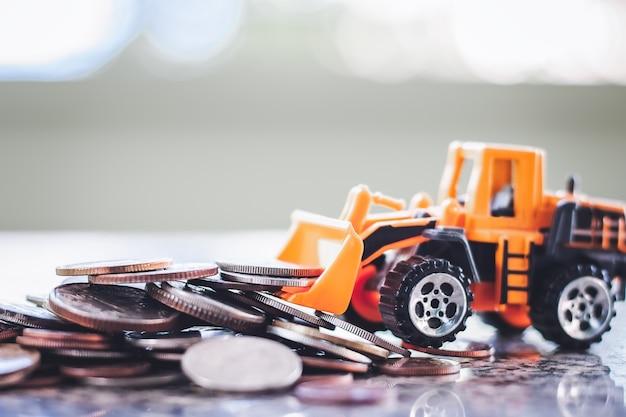 De gele stuk speelgoed bulldozer met stapel van muntstukken tegen vage achtergrond voor het concept van het besparingsgeld