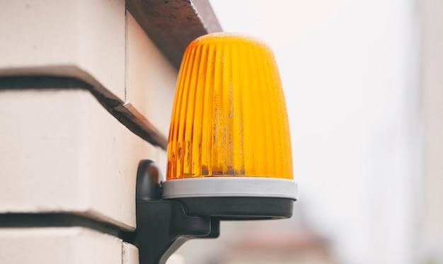 De gele waarschuwingslamp op het hek bedekt met vorst