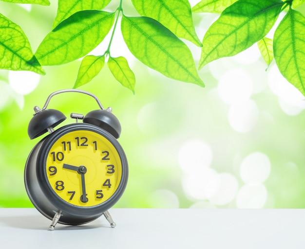 De gele wekker met close-up geeft de tijd weer om half negen