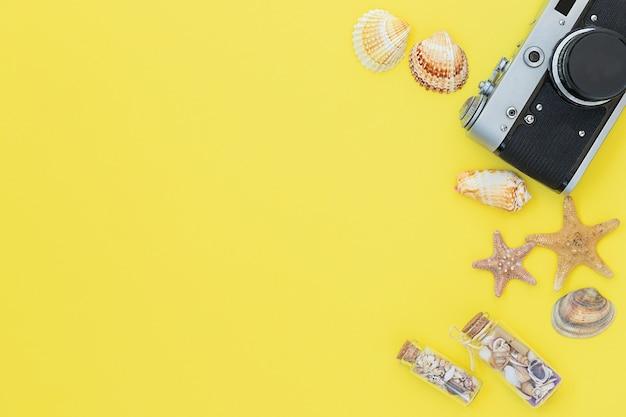 De gele zomerachtergrond met fotocamera schelpen zeesterren