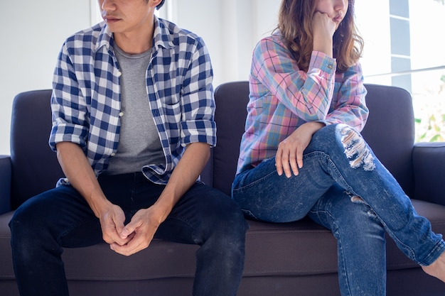 De geliefden zitten verdrietig, praten niet na ruzie, koppige egoïstische man zittend op de bank ongelukkige jonge vrouwen die een slechte relatie beu zijn, verveeld met liefdesproblemen.