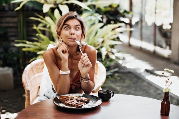 De gelooide gelukkige vrouw in bruine bustehouder kijkt verbaasd, houdt vork vast en maakt grappig gezicht