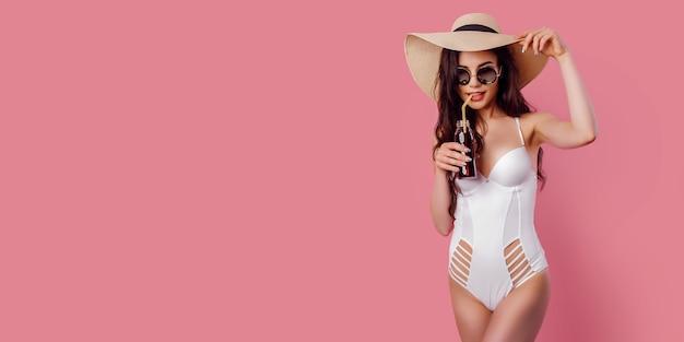 De gelooide jonge vrouw in strohoed, wit zwempak houdt een cocktail op roze achtergrond, isoleert.