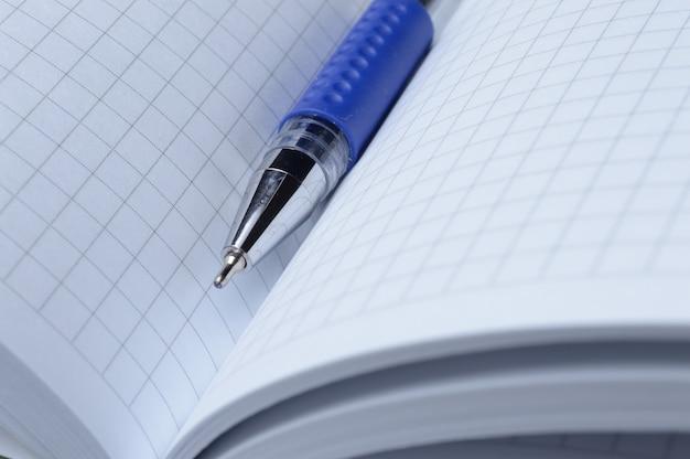 De gelpen ligt op een opengeslagen notitieboekje. detailopname.