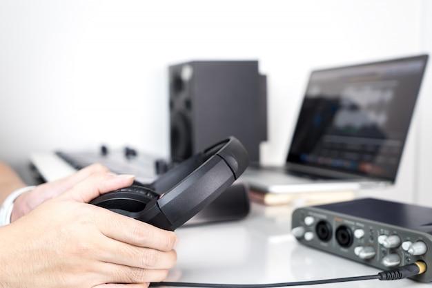 De geluidstechnicus van de muziek houdt een hoofdtelefoon klaar voor het mengen van zitting
