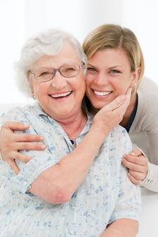 De gelukkige aanhankelijke hogere vrouw omhelst thuis haar kleindochter