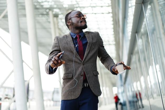 De gelukkige afrikaanse amerikaanse bedrijfsmens danst terwijl hij aan de muziek luistert