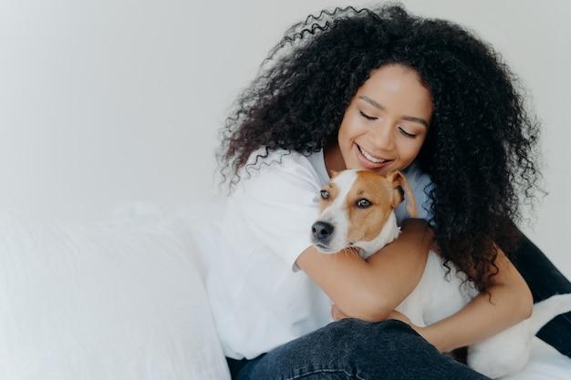 De gelukkige afrikaanse amerikaanse vrouw drukt liefde aan hond uit, omhelst huisdier, gekleed in vrijetijdskleding, zit op comfortabel bed in slaapkamer