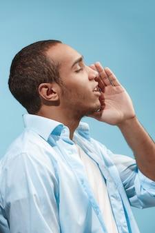 De gelukkige afro-amerikaanse mens schreeuwt tegen blauwe ruimte