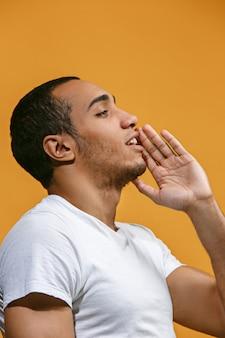 De gelukkige afro-amerikaanse mens schreeuwt tegen oranje ruimte