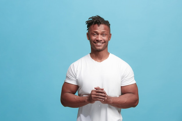 De gelukkige afro-amerikaanse zakenman permanent en lachend tegen blauwe achtergrond.