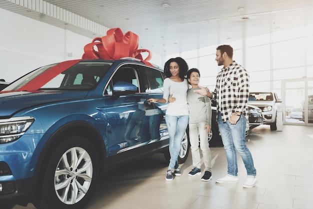 De gelukkige afro-vrouw opent autodeur in autosalon.