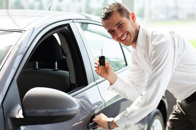 De gelukkige autobezitter toont duimen en zijn nieuwe autosleutel. Premium Foto
