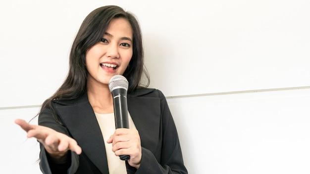 De gelukkige aziatische bedrijfsvrouw die reeks draagt spreekt met microfoon en stelt aan publiek voor.