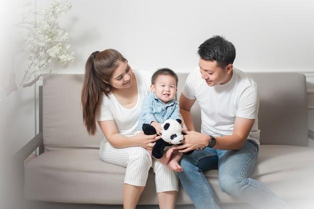 De gelukkige aziatische familie geniet thuis van met zoon