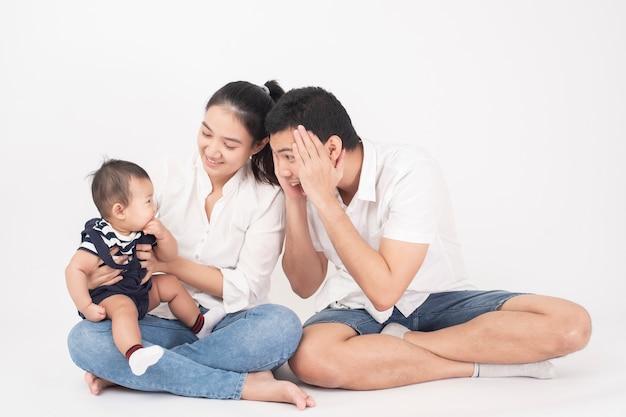 De gelukkige aziatische familie geniet van met zoon in studio