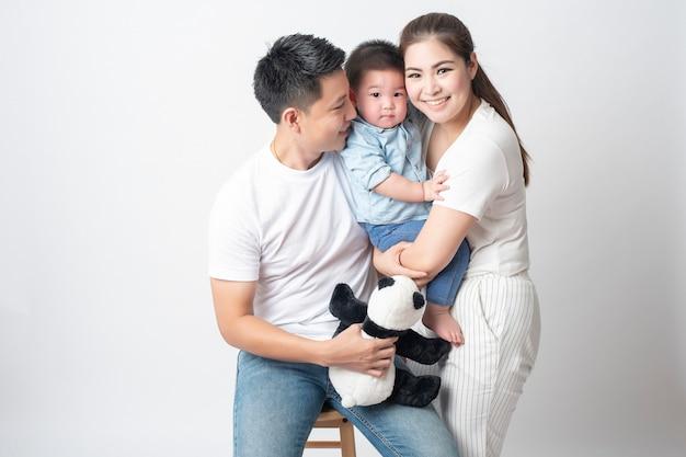 De gelukkige aziatische familie geniet van met zoon