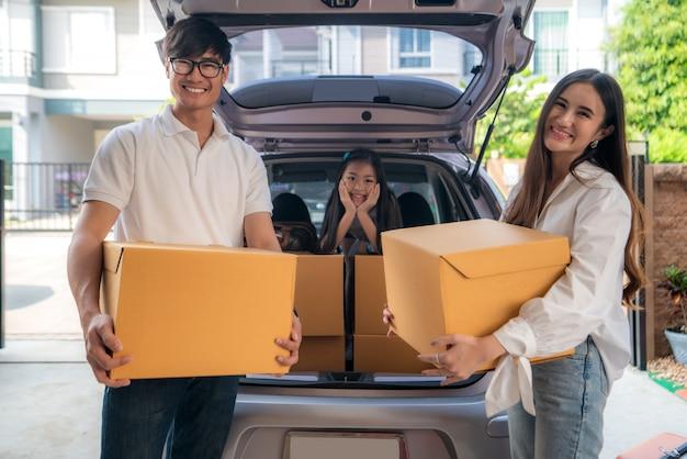 De gelukkige aziatische familie met vader en moeder bevindt zich dichtbij auto met kartondozen en hun dochter glimlachend in auto bij de huisgarage.