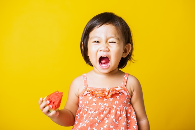 De gelukkige aziatische glimlach van het babymeisje houdt gesneden watermeloen vers voor het eten