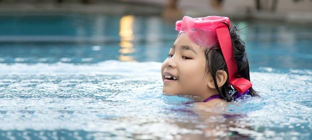 De gelukkige aziatische grote glimlach van het jonge geitje om te spelen zwemt in waterpool bij zomerseizoen