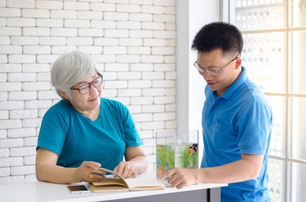 De gelukkige aziatische hogere vrouw die een boek leest en raadpleegt het spreken met haar zoon en goede tijd