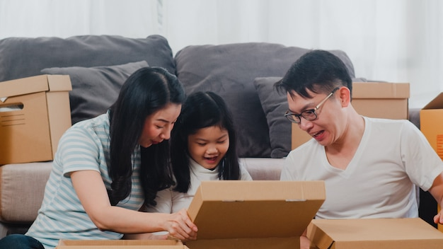 De gelukkige aziatische jonge verhuizingen van de familieverplaatsing regelen in nieuw huis. chinese ouders en kinderen openen kartonnen doos of pakket uitpakken in de woonkamer op verhuisdag. onroerend goed woning, lening en hypotheek.