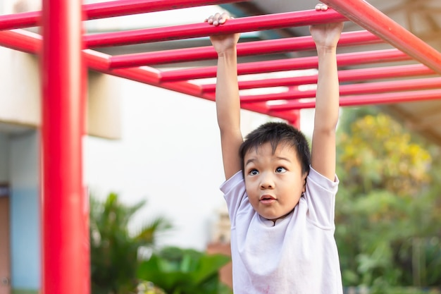 De gelukkige aziatische jongen die van het studentenkind en van een staalbar spelen spelen bij de speelplaats.