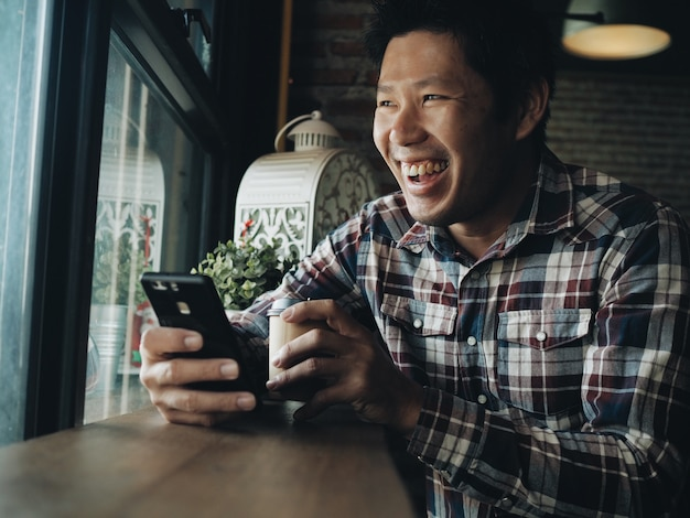 De gelukkige aziatische mens drinkt koffie en gebruikt slimme telefoon in koffiewinkel.