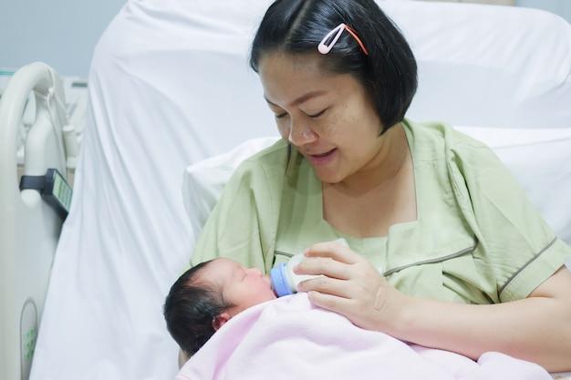 De gelukkige aziatische moeder is flesvoeders voor pasgeboren kleine baby