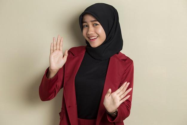 De gelukkige aziatische moslimvrouw zegt hallo op grijze achtergrond