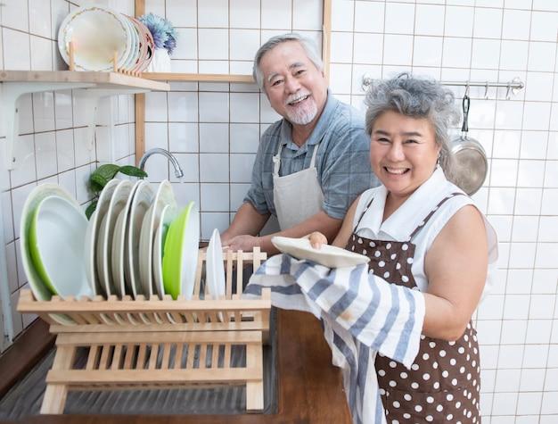 De gelukkige aziatische oudere hogere schotels van de paarwas in gootsteen thuis in keuken thuis.