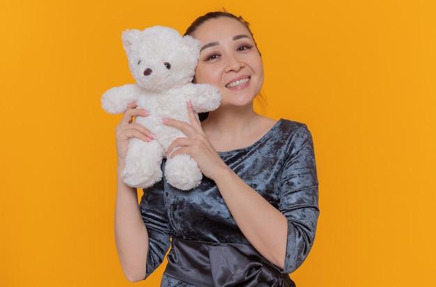 De gelukkige aziatische teddybeer die van de vrouwenholding vrolijk glimlacht kijkt naar voorzijde die de dag van internationale vrouwen viert die zich over oranje muur bevindt