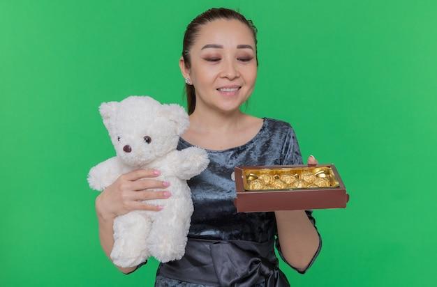 De gelukkige aziatische teddybeer van de vrouwenholding en doos van chocoladesuikergoed als giften die vrolijk de dag van internationale vrouwen vieren die zich over groene muur bevinden