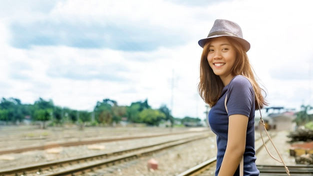 De gelukkige aziatische vrouw gaat in zonnige dag bij spoorweg reizen