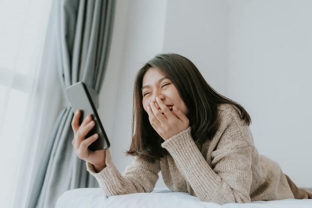 De gelukkige aziatische vrouw geniet van gebruikend smartphone