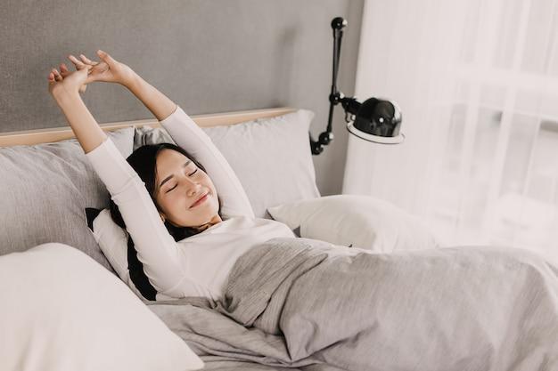 De gelukkige aziatische vrouw glimlacht in ochtend. zij is leugen en strekt hand en lichaam uit op haar bed