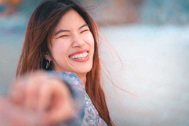 De gelukkige aziatische vrouw houdt hand en trekt haar vriend op een strand