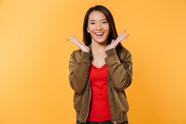 De gelukkige aziatische vrouw in jasjeholding overhandigt dichtbij hoofd