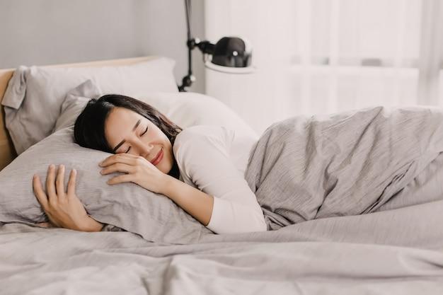 De gelukkige aziatische vrouw rust op zacht hoofdkussen op bed