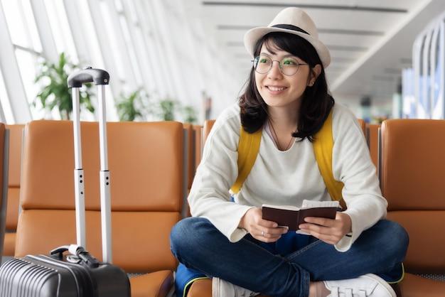 De gelukkige aziatische vrouwenreiziger wacht op de vlucht op de luchthaven.