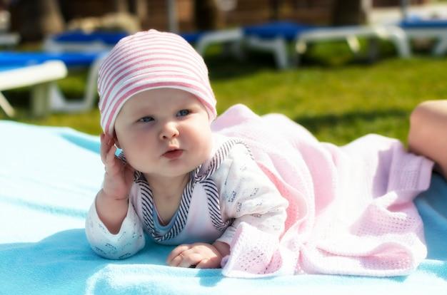 De gelukkige baby die op het strand rusten zonnebank