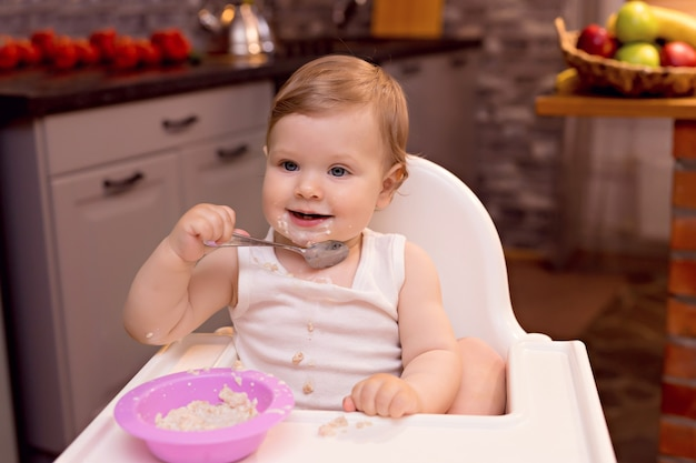 De gelukkige baby eet melkpap met een lepel