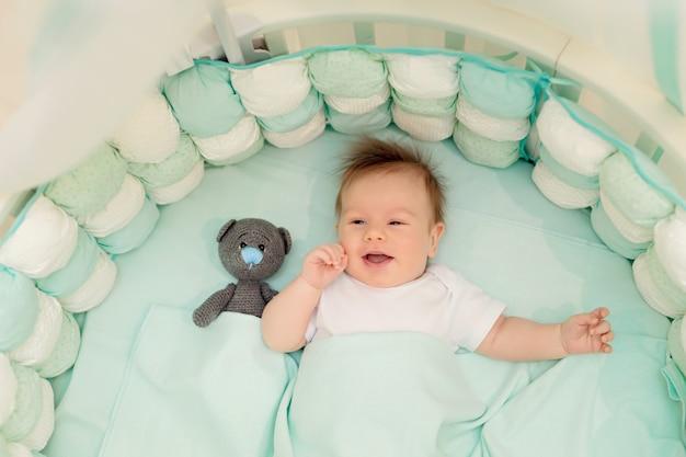 De gelukkige baby ligt op zijn rug in een wit rond bed in de slaapkamer met speelgoed.