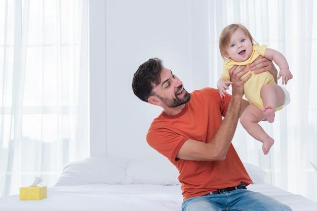 De gelukkige baby van de vaderholding in bed