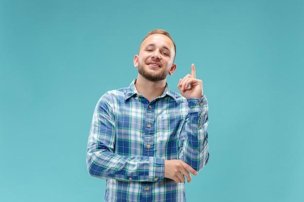 De gelukkige bedrijfsman die en zich tegen blauwe muur bevindt glimlacht