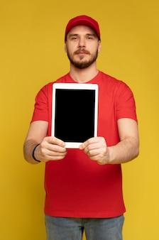 De gelukkige bezorger met tablet in studio isoleerde gele muur