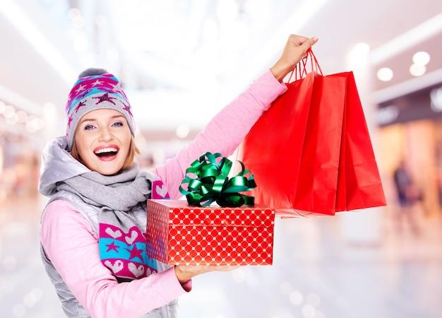 De gelukkige blanke vrouw met geschenken na het winkelen