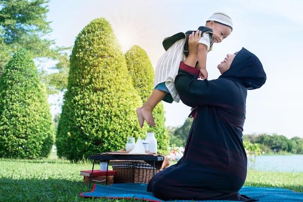 De gelukkige blije aziatische moslimmoeder die pret hebben werpt op haar zoon in de lucht, het moslimmamma en het zoonconcept